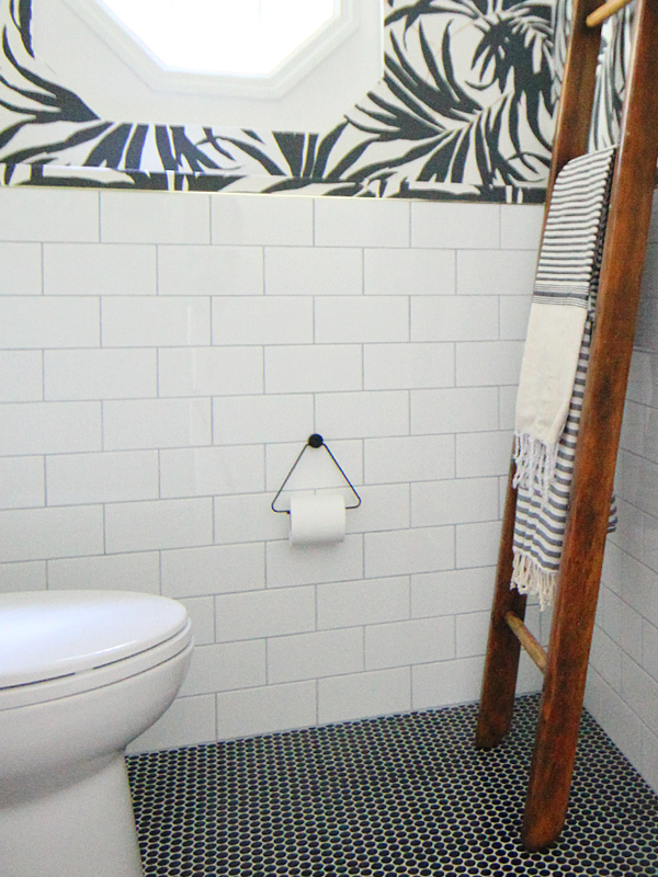 Basement Bathroom Makeover - White subway tile and black penny tile on the floor pairs with bold black and white palm leaf wallpaper.Turkish towels hang off a vintage wooden ladder — House Of Hipsters
